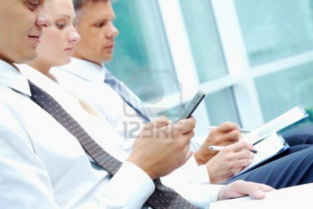 7509013-image-of-businessman-writing-sms-at-conference-with-working-partners-on-background